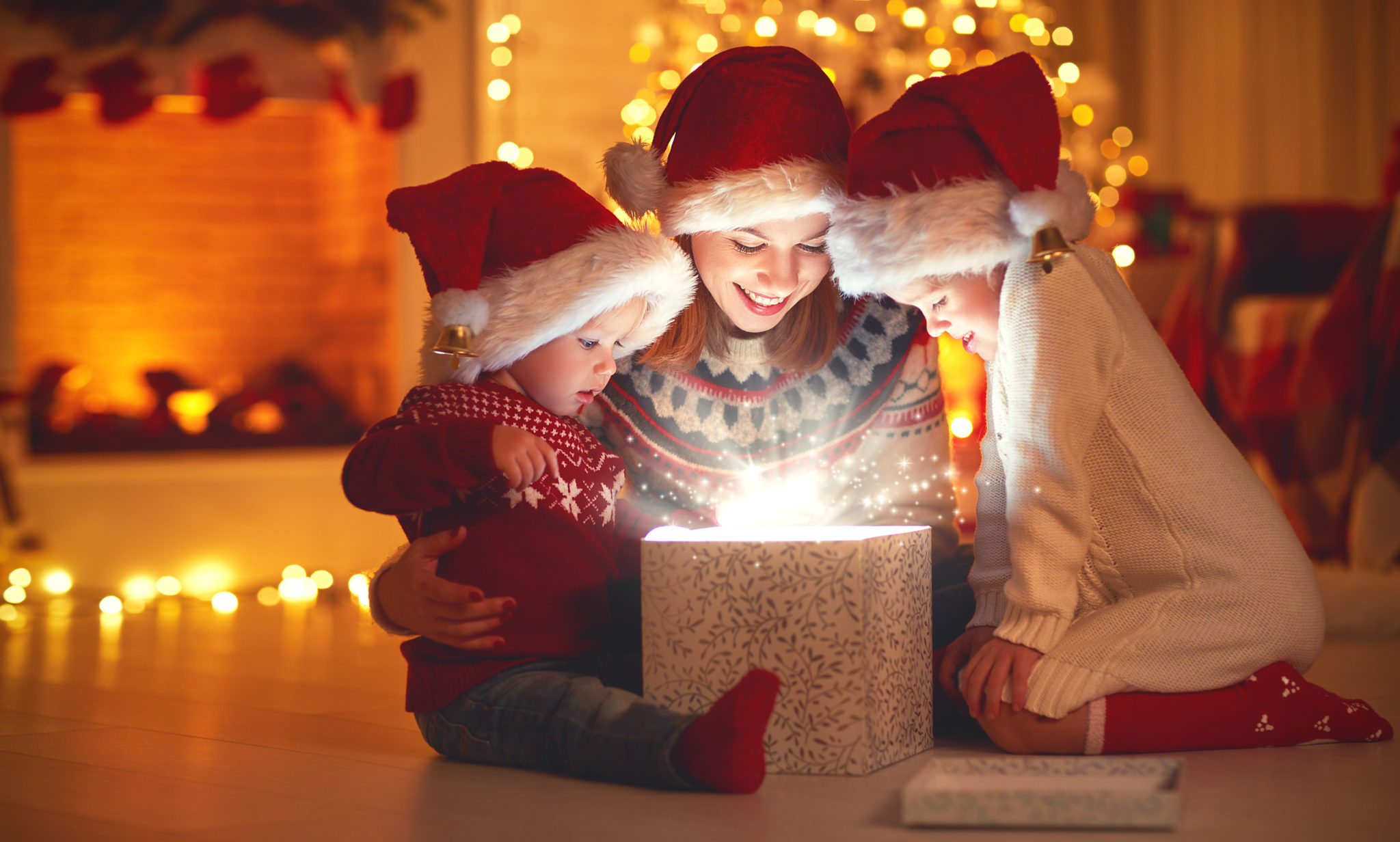 Merry Christmas! family mother and children with magic gift at home ...